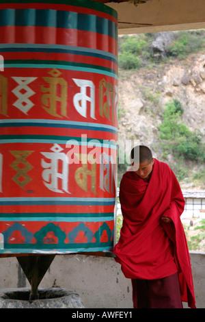 Tibetan monk praying with a spinning prayer wheels, Bhutan - Stock Photo