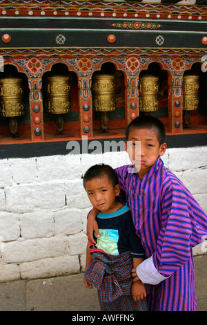 Portrait of a couple of children with the spinning praying wheel in the background, Thimphu, Bhutan - Stock Photo