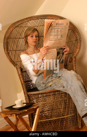 young woman reading the FT in casual clothes - Stock Photo