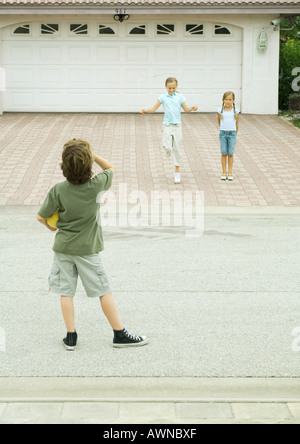 Two girls playing in driveway while boy watches from street, hoolding ball - Stock Photo