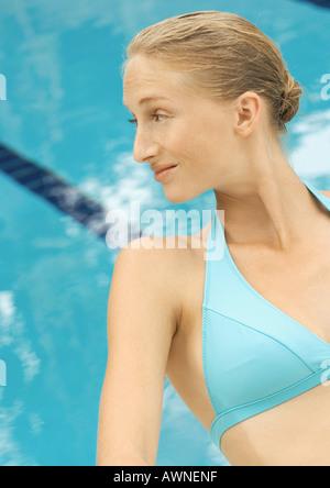 Woman in bikini sitting by pool - Stock Photo