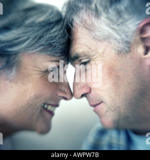 Profile of man and woman head to head with noses touching - Stock Photo