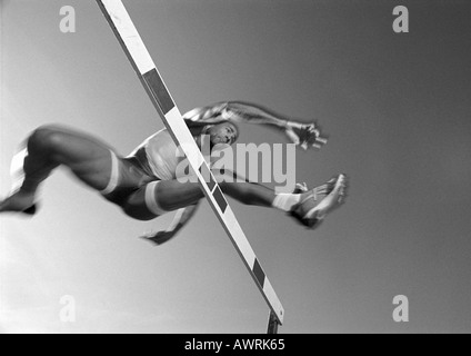 Male athlete jumping hurdle, low angle view, blurred motion, b&w - Stock Photo