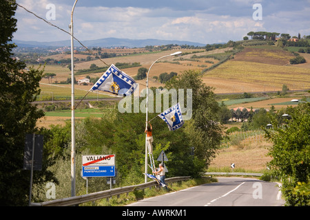 Dogana Contrada members hang flags from light poles along highway approaching the Tuscan village of Valiano Italy - Stock Photo