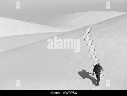 Man hiking up sand dune, rear view, b&w - Stock Photo