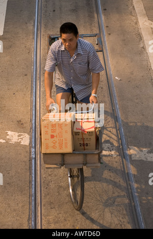 dh Hennessey Road CAUSEWAY BAY HONG KONG Man riding bicycle in between tram tracks delivery cycle chinese worker - Stock Photo