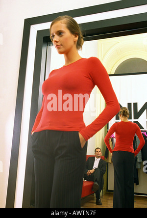 Woman trying on outfit in shop, showing boyfriend - Stock Photo