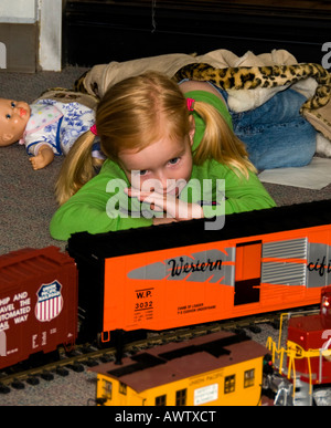 A young girl watched a miniature train run on a track at a train show - Stock Photo