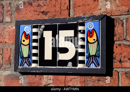 Fishy number plate on brick wall - Stock Photo