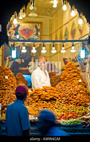 Vertical portrait of an elderly man serving behind a display of traditional Morrocan sweets & pastries in Rue Souk - Stock Photo