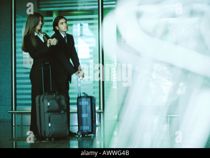 Man and woman standing with suitcases, woman looking at watch. - Stock Photo