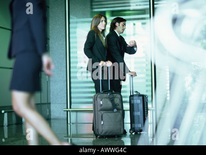 Man and woman standing with suitcases, man looking at watch. - Stock Photo