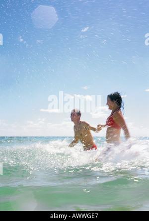Couple splashing in sea - Stock Photo