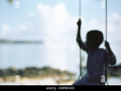 Silhouette of child sitting on swing, blurred - Stock Photo