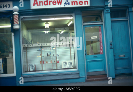 Exterior of old fashioned Gentlemen's Hairdresser shop with barbers striped pole above window - Stock Photo