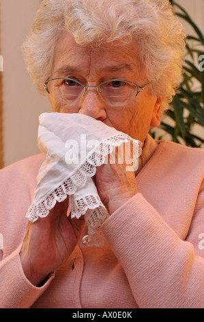 Elderly woman bowing her nose with a cloth handkerchief - Stock Photo