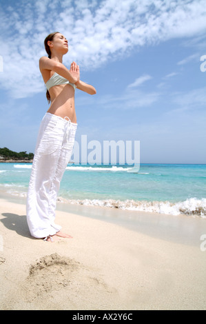 Beach wellness young woman doing a yoga excercise well being wellbeing wellness serene fit fitness vitality - Stock Photo
