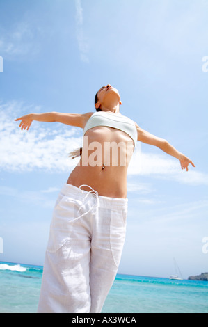 Beach wellness young woman doing a yoga excercise Sun woman beach holiday lifestyle relax summer - Stock Photo