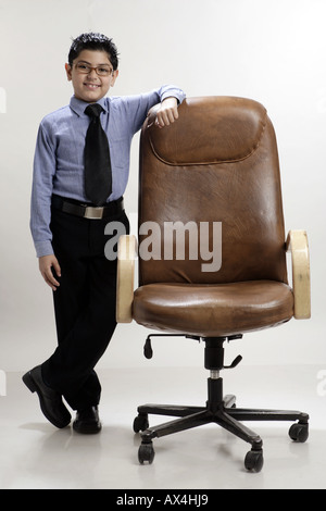 Portrait of a boy pretending like a chairman and smiling - Stock Photo