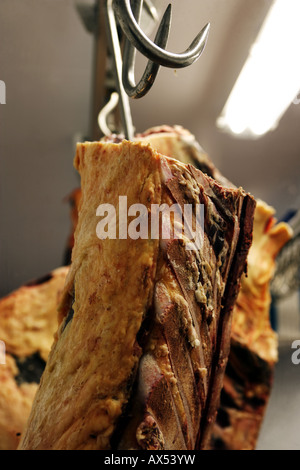 Organic beef carcasses / carcases hang on butcher's hooks in a farm freezer room - Stock Photo
