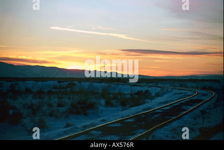 A gorgeous wintertime sunset in Salt Lake City, Utah, USA with a set of old railroad tracks going off into the sunset - Stock Photo