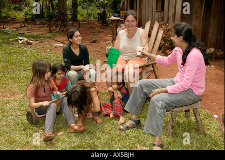 Work break in front of the house, women with children, Asuncion, Paraguay, South America - Stock Photo