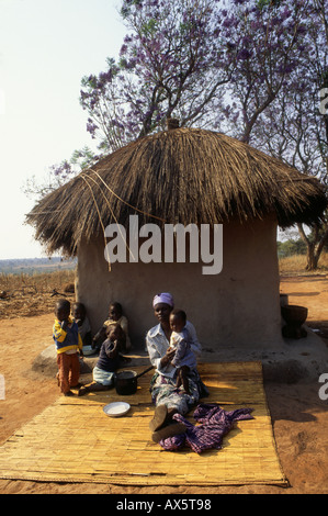 Kapatu, Zambia. Woman with her five children outside their thatched adobe house sitting on reed mats. - Stock Photo