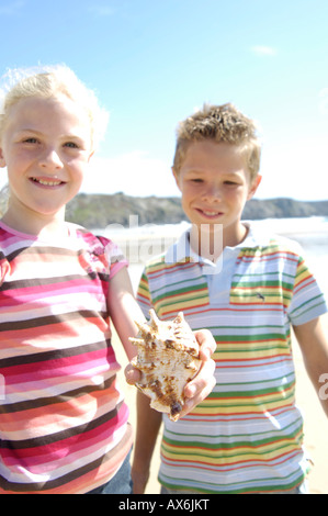 Portrait of girl holding shell with boy standing beside her on beach - Stock Photo