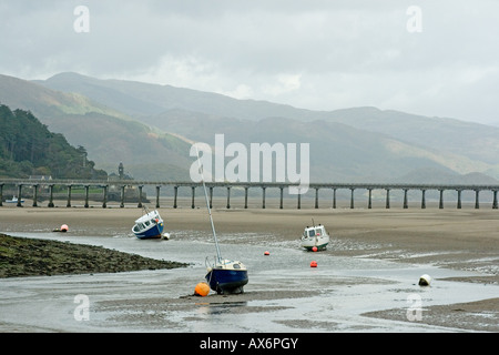 Boats high and dry on the Mawddach Estuary with railway bridge and mountains beyond as backdrop - Stock Photo