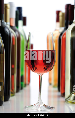 Glass of red wine between wine bottles, close-up - Stock Photo