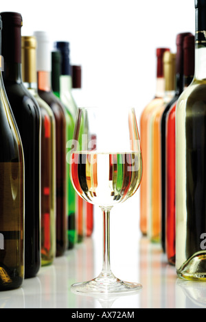 Glass of white wine between wine bottles, close-up - Stock Photo