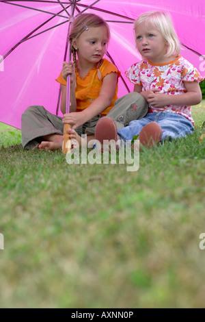 Two little girls sitting under a pink umbrella - Stock Photo