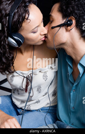 Portrait of a couple kissing while wearing headphones and ear pieces. - Stock Photo