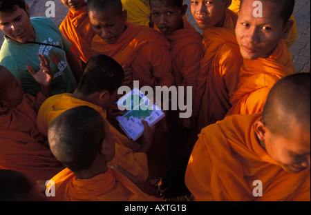 Phnom Penh a group of monks on the Sisowath Quay shelping a tourist finding his way - Stock Photo