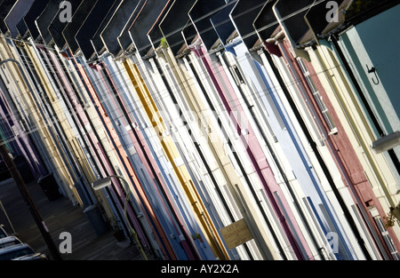 Terrace of Victorian houses in pastel colours on a hilly street in Brighton - Stock Photo