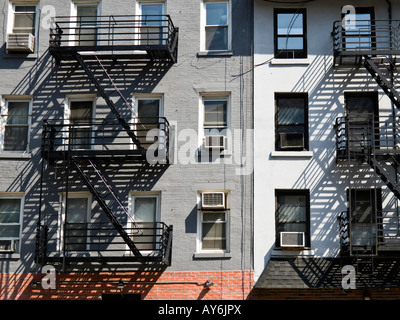 Black iron fire escapes on older brick apartment buildings in New York City - Stock Photo