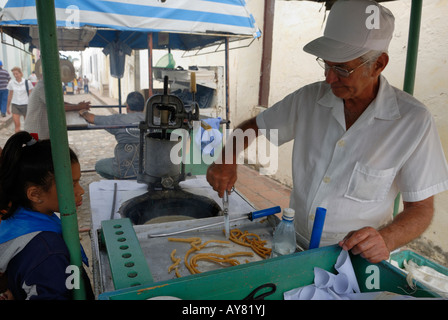 A street vendor selling sweets to a little girl in Sancti Spiritus, Cuba April 2007 - Stock Photo