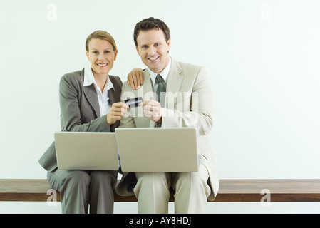 Man and woman sitting, holding credit card together, both dressed in suits with laptop computers - Stock Photo