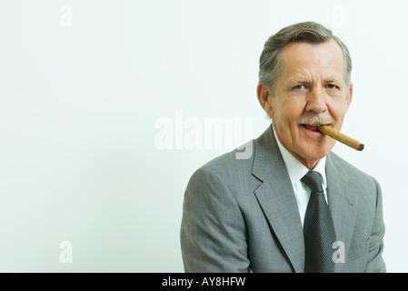 Businessman smoking cigar, smiling at camera, portrait - Stock Photo