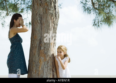 Two sisters playing hide-and-seek, one covering eyes with hands, the other peeking around tree trunk - Stock Photo