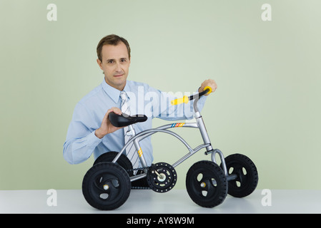 Man holding child's bicycle, looking at camera - Stock Photo