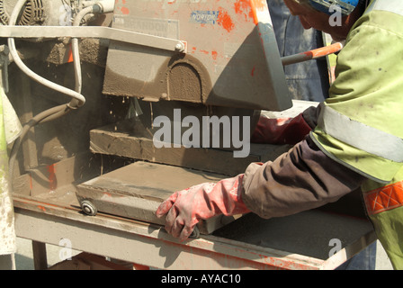 Close up of workman using a powered high speed circular cutting disc to saw through concrete paving slabs for street - Stock Photo