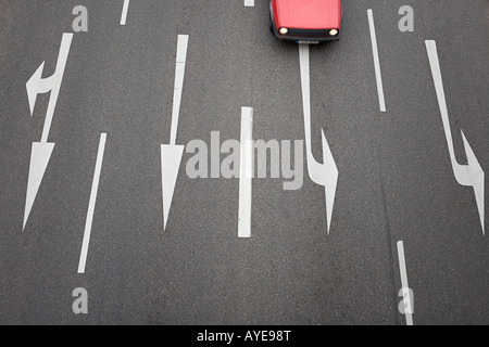 Arrow signs on a road and a car - Stock Photo