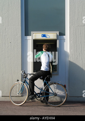 Rear view of a young man on bicycle withdrawing cash at bank's ATM, Colmar, Alsace, France - Stock Photo