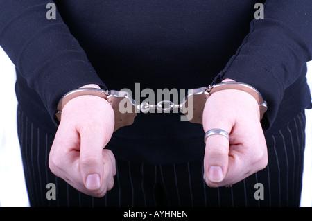 Woman in handcuffs (close-up focus on hands) / Junge Frau in Handschellen - Stock Photo