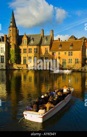 Canal and sightseeing cruise boat in central Bruges Belgium Europe - Stock Photo