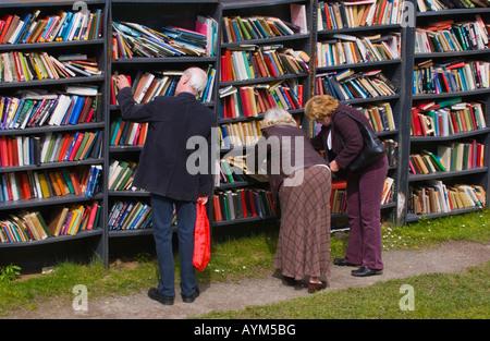 Openair Hay Castle Honesty Bookshop Hay on Wye Powys Wales UK EU people browsing shelves filled with hardback & - Stock Photo