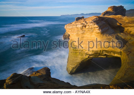 Pacific Ocean waves created an arch in the sandstone cliffs of Cape Kiwanda near Pacific City, Oregon. - Stock Photo
