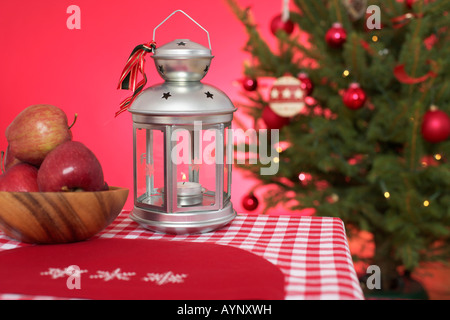 Christmassy decorated table with lantern, Christmas tree in background - Stock Photo