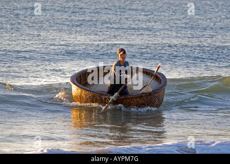 Vietnamese fisherman in his basket boat on the beach at Mui Ne, Vietnam, Southeast Asia, Asia - Stock Photo